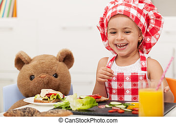 Little happy girl having a snack with her teddy bear