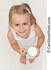 Little happy girl holding a cup of milk - top view