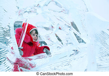 Little happy girl in red warm clothes in ice sculpture - ...