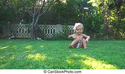 Little happy girl jumping and falling at backyard in sunny...