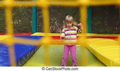 little happy girl jumping on inflatable trampoline in amusement park behind net