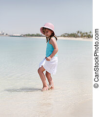 Little happy girl on the beach
