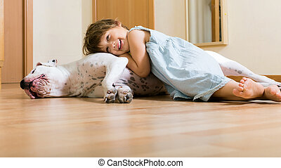 little happy girl on the floor with dogo Argentino (focus on...
