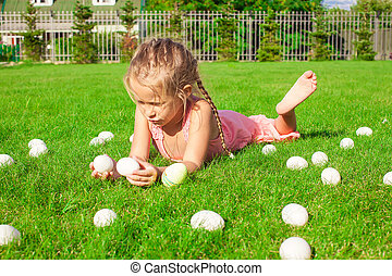 Little happy girl playing with white Easter eggs on green grass