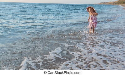 Little happy girl running along the seashore to her parents in slow motion
