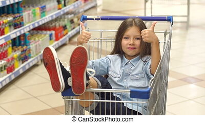 Little happy girl sits in a grocery cart in a supermarket and shows her thumb up