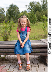 Little happy girl sitting on a bench
