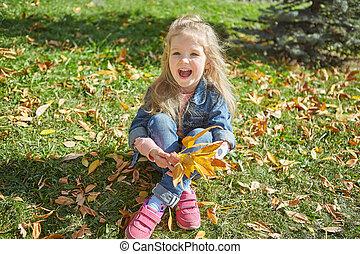 Little happy girl sitting on grass on autumn sunny day.
