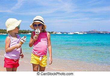 Little happy girls eating ice cream on tropical beach