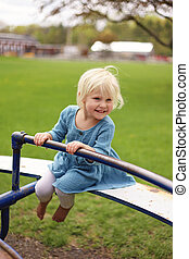 Little Happy Todler Girl Riding Merry Go Round at Park Playground