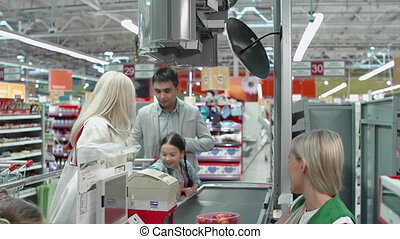 Pedestal down of family of four at the cash desk, parents and girl putting merchandise on conveyor belt, her sister packing things