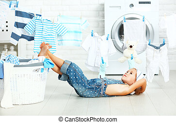 little helper tired child girl to wash clothes and rest in the laundry room