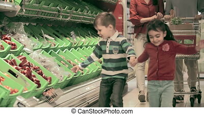 Little Helpers - Family of four shopping for sweet pepper,...