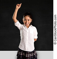 little Hispanic schoolgirl rising hand up to answer the teacher
