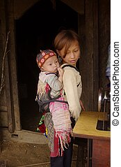 Little Hmong girl carrying in back - Since their very young...