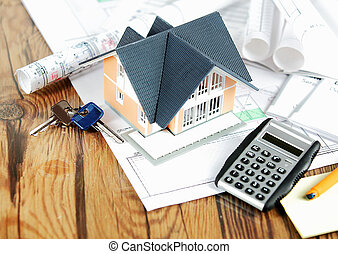 Little Home on Blueprints with Keys and Calculator - Close...