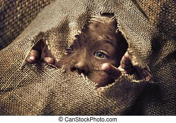 Little homeless boy wearing a bag - Little homeless child...