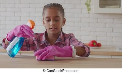 Little housekeeping girl cleaning with spray detergent - ...