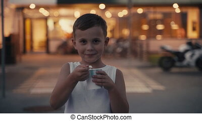 Little hungry boy eating ice cream on the evening street