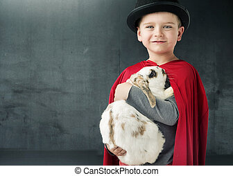 Little illusionist holding a magic rabbit
