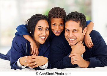 little indian boy hugging his parents while lying on bed