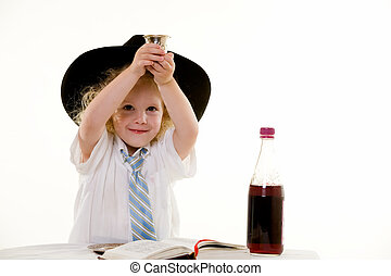 Portrait of an adorable curly haired blond little three year old boy wearing white shirt and tie and a black fedora practicing the Jewish Sabbath ritual raising up wine glass