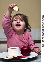 Little Jewish girl dipping apple slices into honey. It's the...
