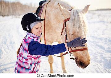 Little jockey - Little girl in jockey helmet touching horse...