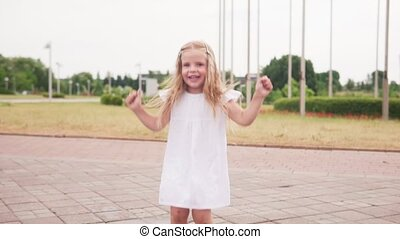 Little joyful barefoot girl jumping in puddle and having...