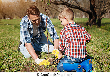 Little kid and his father gardening together - Maintaining...