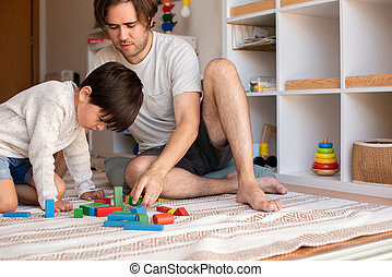 kid and his father playing at home with wood building blocks. Homeschooling. Stay at home. Family time
