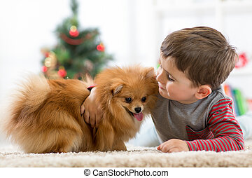 Little kid boy with dog lying on the floor at christmas tree