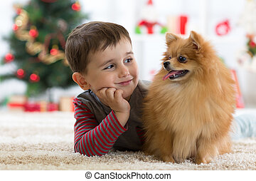 Little kid boy with dog lying on the floor in festival room