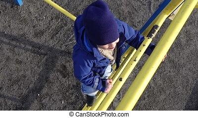 Little kid climbing up on ladder in playground