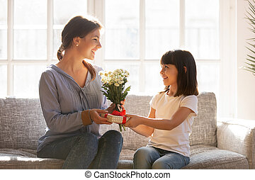 Little kid daughter giving mom receiving gift box and flowers