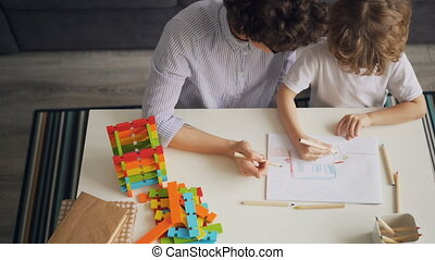 Little kid drawing and colouring picture with careful mother at table at home