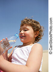 Little kid drinking bottle of water at the beach