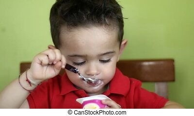 little kid enjoying his yogurt - young boy eating yogurt at...