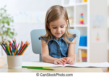 Little kid girl draws sitting at table in room in nursery