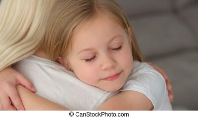 Happy cute affectionate adopted little kid girl hugging foster care parent mother with eyes closed, adorable small child daughter embrace mum cuddling enjoy tender sweet moment concept, close up view