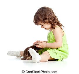 Little kid girl strokes kitten. Isolated on white background
