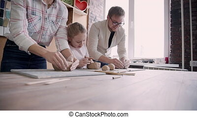 Little kid girl with her charming family making craft...