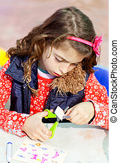 little kid girl working at school doing workshop