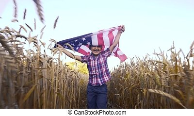 Little kid holding an American flag on the wind in a field of wheat. Summer landscape against the blue sky.