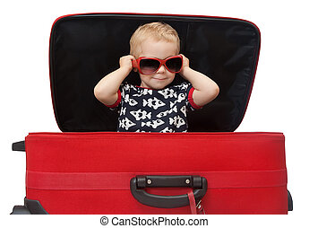 Little kid in sunglasses looking out red suitcase