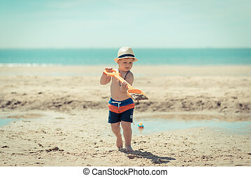 little kid is running in the sand