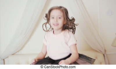 little kid jumping and dancing on the bed