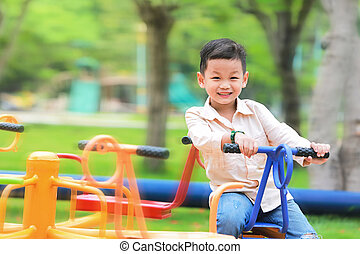 Little kid playing carousel in the park with happy and smiling.