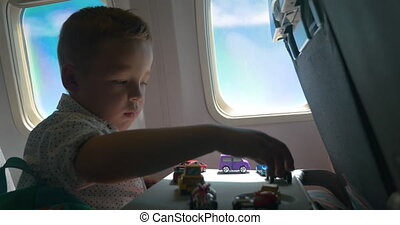 Little kid playing with toy cars in the airplane