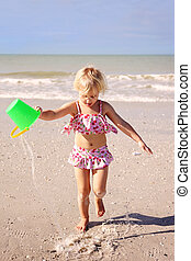 Little Kid Running on The Beach by The Ocean with a Bucket of Water